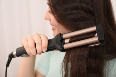 Young woman using modern curling iron against light background, focus on device