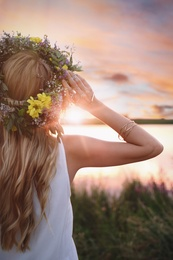 Young woman wearing wreath made of beautiful flowers outdoors at sunset