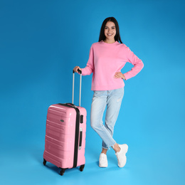 Beautiful woman with suitcase for summer trip on blue background. Vacation travel