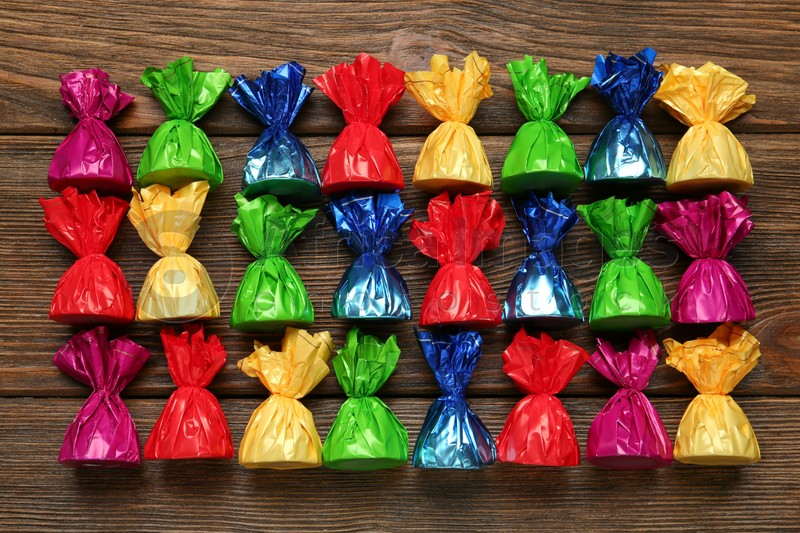 Many candies in colorful wrappers on wooden table, flat lay