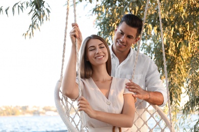 Young woman in hammock chair and her boyfriend on beach. Summer vacation