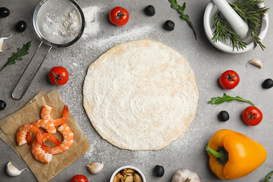 Flat lay composition with dough and fresh ingredients for seafood pizza on grey table