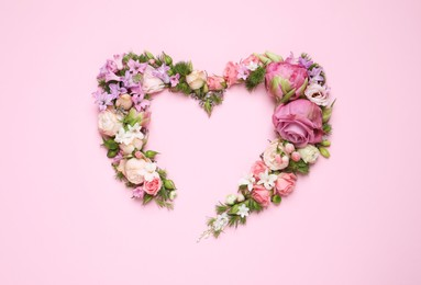 Beautiful heart made of different flowers on pink background, flat lay. Space for text