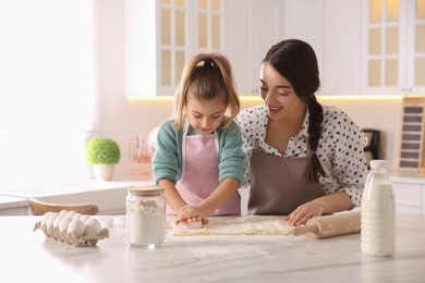 Mother and daughter making pastry in kitchen at home