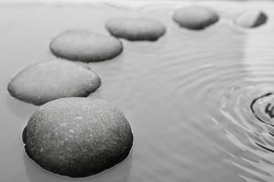 Beautiful spa stones in water, space for text. Zen lifestyle