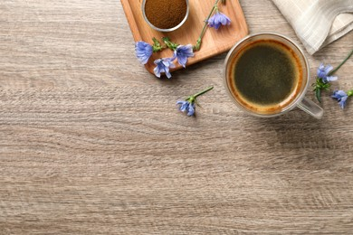 Glass cup of delicious chicory drink, powder and flowers on wooden table, flat lay. Space for text