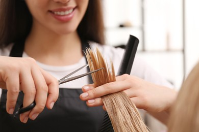 Stylist cutting hair of client in professional salon, closeup