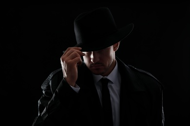 Old fashioned detective in hat on dark background