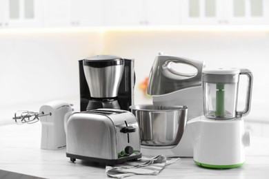 Modern toaster and other cooking appliances on table in kitchen