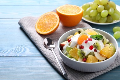 Delicious fruit salad on light blue wooden table, space for text