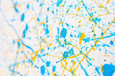 Colorful paint splashes on white canvas as background. Art and creativity