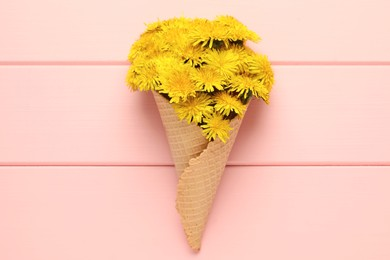 Beautiful yellow dandelions in waffle cone on pink wooden table, top view