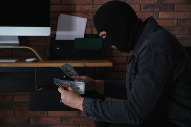 Dangerous masked criminal stealing money from house