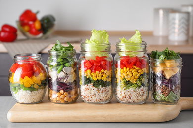 Glass jars with healthy meal on light grey table