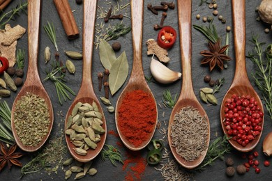 Flat lay composition with different natural spices and herbs on black table