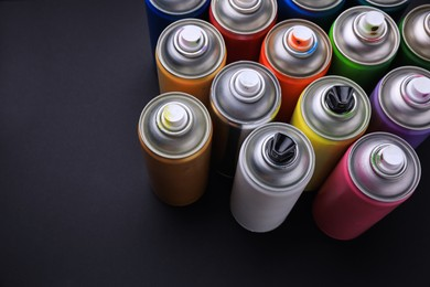 Cans of different graffiti spray paints on black background, above view
