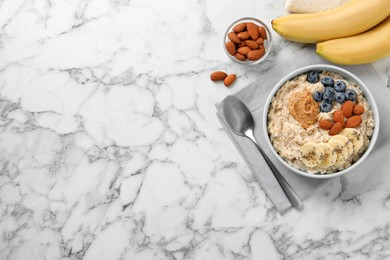 Tasty oatmeal porridge with toppings served on white marble table, flat lay. Space for text