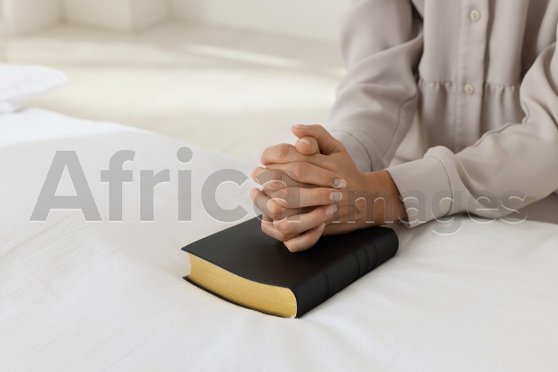 Religious woman with Bible praying in bedroom, closeup