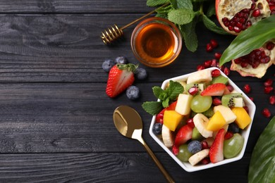 Delicious fresh fruit salad in bowl on black wooden table, flat lay. Space for text