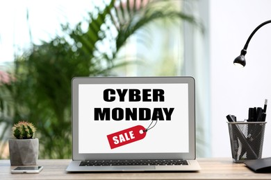 Modern laptop with text Cyber Monday Sale on screen in room