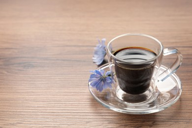 Glass cup of delicious chicory drink and flowers on wooden table, space for text