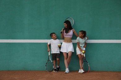 Young woman with her cute children near green wall on tennis court