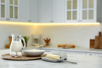 Different dairy products and eggs on white table in modern kitchen. Space for text