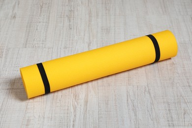 Bright rolled camping mat on white wooden background