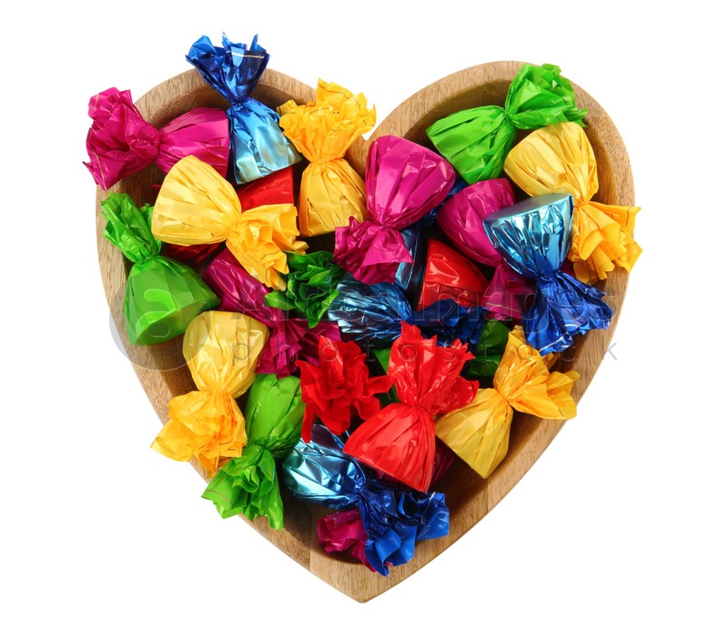 Heart shaped plate with candies in colorful wrappers isolated on white, top view