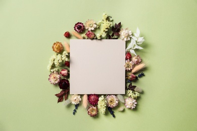 Flat lay composition with dried flowers and blank card on green background. Space for text