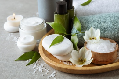Spa composition with skin care products on textured table, closeup