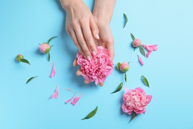 Woman holding beautiful peony flower on color background, top view