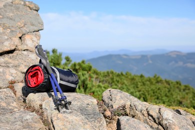 Sleeping bag and trekking poles on mountain peak, space for text