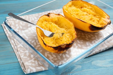 Halves of cooked spaghetti squash and fork in baking dish on turquoise wooden table, closeup