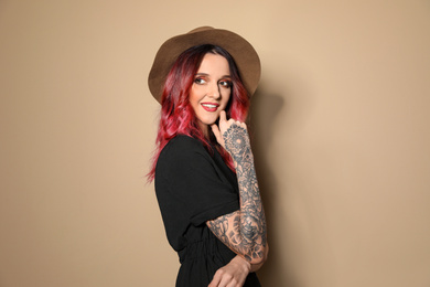 Beautiful woman with tattoos on arms against beige background
