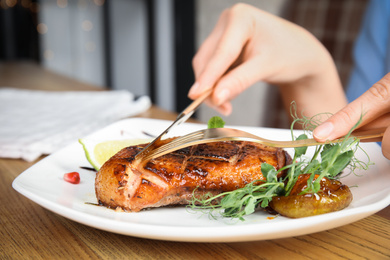 Woman eating delicious grilled duck breast served at wooden table, closeup
