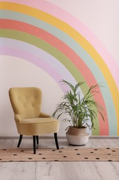 Comfortable chair, runner rug and houseplant near white wall with rainbow art indoors
