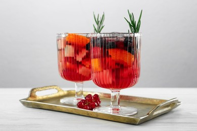 Glasses of Red Sangria on white wooden table against light grey background