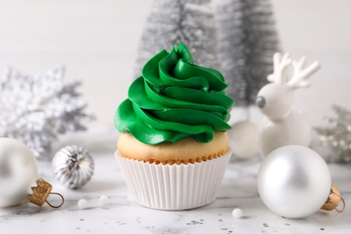 Delicious cupcake with green cream and Christmas decor on white marble table