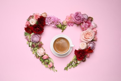 Beautiful heart shaped floral composition with cup of coffee on pink background, flat lay