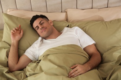 Man sleeping in bed with green linens at home