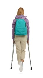 Young woman with axillary crutches on white background, back view