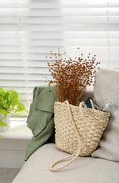 Stylish beach bag with wildflowers, bottle of water and book on sofa in room