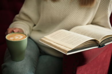 Woman with cup of coffee reading book indoors, closeup