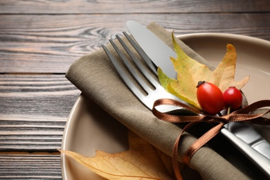 Festive table setting with rosehip berries and autumn leaves on wooden background, closeup. Thanksgiving Day celebration