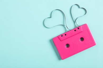 Top view of music cassette and hearts made with tape on turquoise background, space for text. Listening love song