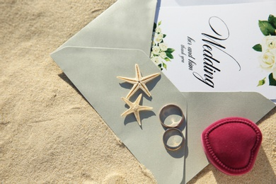 Flat lay composition with wedding invitation and gold rings on sandy beach