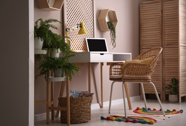 Comfortable workplace with modern laptop and houseplants in room. Interior design