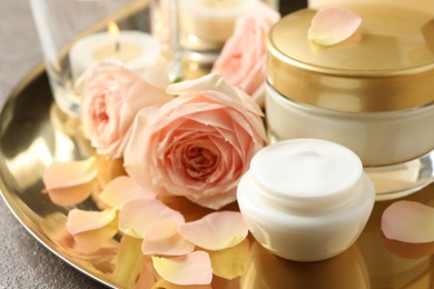 Composition with skin care products and roses on golden tray, closeup
