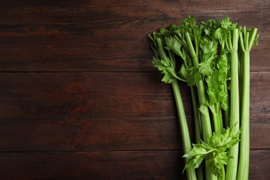 Fresh green celery on wooden table, top view. Space for text